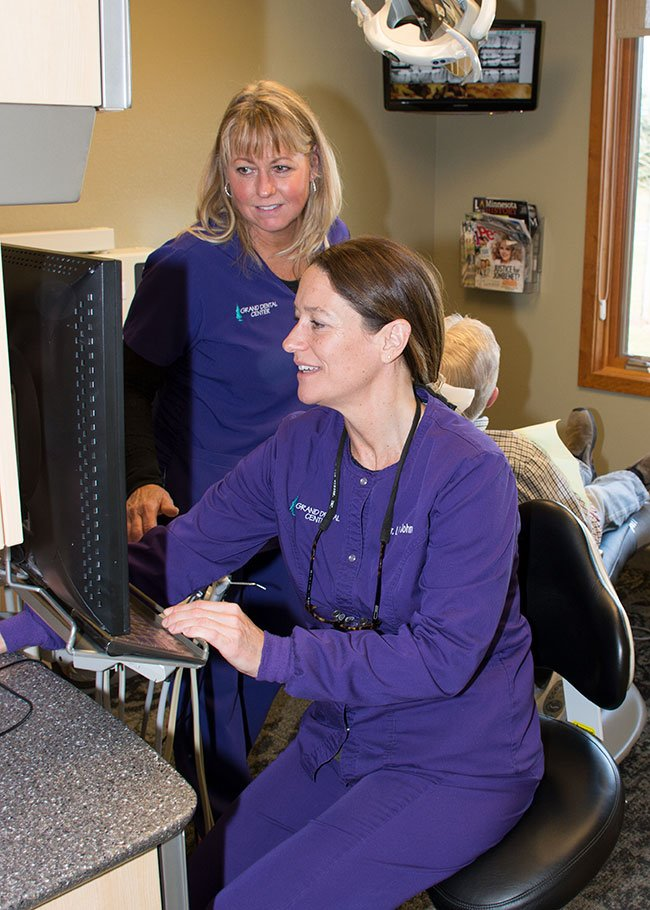 Dr. Lisa Johnson discusses a patient dental bridge with her assistant Renee Neustrom.